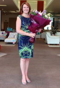 Louise Jenner stands in her dfs showroom holding a bouquet of flowers on her last day at work