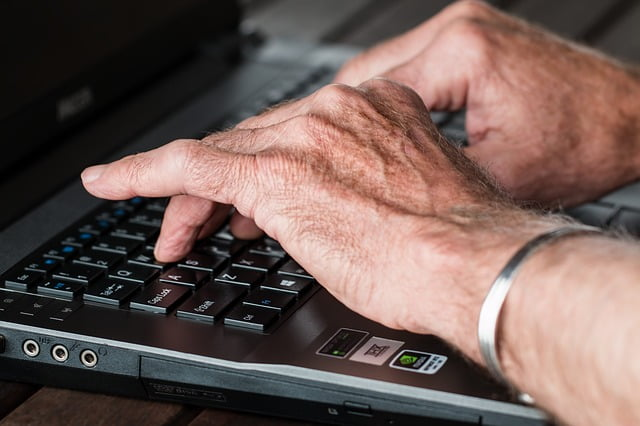 Man's hands typing on a laptop computer
