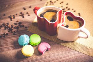 Two heart shaped coffee mugs with a scattering of coffee beans in the background and some brightly-coloured macaroons in the foreground.