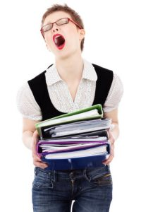Woman screaming with frustration, holding a stack of files.