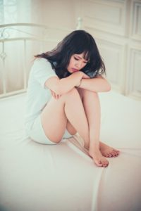 Young woman sitting on her bed, looking very sad and emotional.