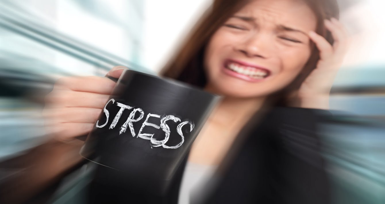Woman holding a mug with the word STRESSED printed on it.